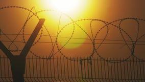 Regime rigoroso della prigione del recinto il filo spinato della siluetta recinto di immigrazione clandestina dai rifugiati Immig archivi video