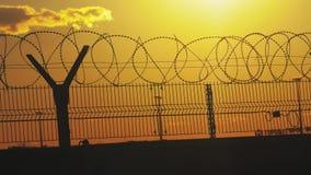 Regime rigoroso della prigione del recinto il filo spinato della siluetta recinto di immigrazione clandestina dai rifugiati Immig video d archivio