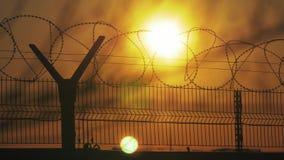 Regime rigoroso della prigione del recinto il filo spinato della siluetta recinto di immigrazione clandestina dai rifugiati stile archivi video