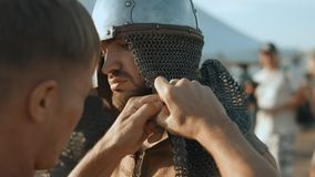 Regimentals of the ancient warrior. Soldier wearing the helmet with chain mail and fix it stock footage