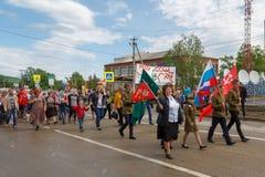 Regimento imortal, parada com as bandeiras vermelhas no dia da vitória com a participação dos alunos e pais Imagens de Stock