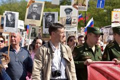 Regimento imortal - pessoa com os retratos de seus parentes, participantes na segunda guerra mundial, na parada de Victory Day fotos de stock royalty free
