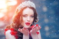 Regina della neve nel rosso Donna di inverno in corona in un vestito ed in un rosso rossi Fotografie Stock