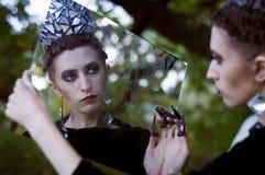 Regina diabolica che guarda nello specchio Immagine Stock Libera da Diritti