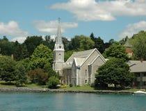 Regione dei laghi finger: Chiesa fronta e Steepl del lago Fotografie Stock Libere da Diritti