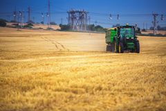 Regione di Varna, Bulgaria - 20 giugno 2015: Trattore di John Deere 6115R con il rimorchio su un campo giallo Immagini Stock Libere da Diritti