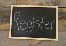 Register for classes concept. Register written in chalk on a chalkboard on a rustic background Stock Image