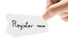 Register now. Concept using a hand holding a piece of paper and the text written by hand with a permanent marker Royalty Free Stock Photography
