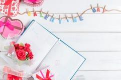 Registi il libro il 14 febbraio con il mazzo del contenitore e della rosa rossa di regalo Fotografia Stock
