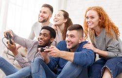 Registrador y cuervo Amigos que juegan a los videojuegos, divirtiéndose imagenes de archivo