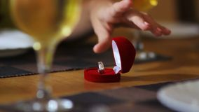 Registrar takes ring from table to navigate wedding ceremony. Closeup registrar takes silver ring from table between two glasses of champagne to navigate wedding stock footage