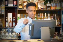 registrating新的命令的餐馆工作者由收款机 免版税图库摄影