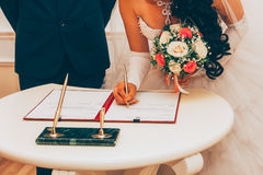 Registration Of Marriage, The Bride With A Bouquet Of Flowers Signed A Marriage Contract Royalty Free Stock Photography