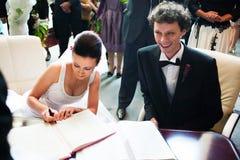 Registrazione di firma dello sposo e della sposa Immagini Stock Libere da Diritti