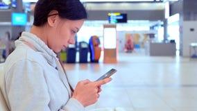 Registrazione online di registrazione della donna sul suo telefono cellulare nel corridoio dell'aeroporto, vista laterale stock footage