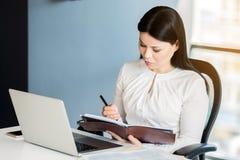 Registrazione sicura seria di signora di affari qualcosa in suo giornale Immagini Stock Libere da Diritti
