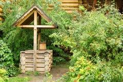 Registre bem com cubeta e as decorações cinzeladas de madeira Fotografia de Stock