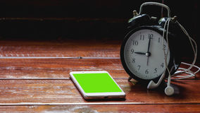Registre con los teléfonos móviles y los auriculares blancos en un escritorio de madera por un día de fiesta Imágenes de archivo libres de regalías