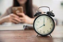 Registre con smartphone que juega adolescente de la muchacha de la falta de definición mientras que libro de lectura fotografía de archivo