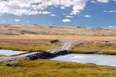 Registre el puente de madera a través del río blanco rápido de la montaña en un fondo de las colinas amarillas del desierto Fotografía de archivo