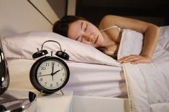 Registre el reloj y a la mujer del ` de la demostración 2 O que duermen en cama Foto de archivo