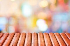 Registre el tablero de la mesa de madera con el fondo colorido borroso de la luz del bokeh, imágenes de archivo libres de regalías