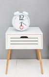 Registre en un nightstand blanco cerca de la pared gris Fotografía de archivo libre de regalías