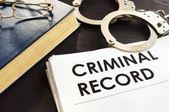 Registro criminal e algemas em uma mesa fotos de stock