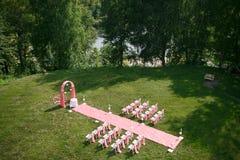 Registro de la boda hermoso en naturaleza Sillas blancas para el registro que visita Tienda rosada con las flores blancas para Fotos de archivo libres de regalías