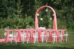 Registro de la boda hermoso en naturaleza Sillas blancas para el registro que visita Tienda rosada con las flores blancas para Imagen de archivo