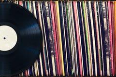 Registro de vinil com espaço da cópia na frente de uma coleção dos álbuns (títulos do manequim) Foto de Stock Royalty Free