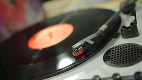 Registro de vinil que gira no jogador de música retro na loja dos instrumentos musicais do vintage filme