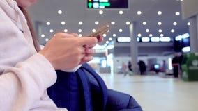 Registro em linha do registro da mulher em seu telefone celular no salão do aeroporto, mãos com close-up do smartphone filme