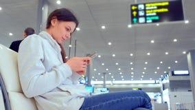 Registro en línea en su teléfono móvil en pasillo del aeropuerto, vista lateral del enregistramiento de la mujer almacen de metraje de vídeo