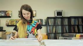 Registros bonitos do vintage da consultação da jovem mulher na loja do vinil video estoque