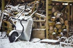Registros de la leña y una carretilla en una vertiente de madera vieja en el sno Imagenes de archivo