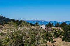 Registros de madera del bosque de pino en el bosque y una casa blanca distante Montañas de apertura de sesión de Pindus Imagen de archivo libre de regalías