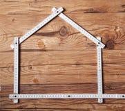 Regla de plegamiento que forma una casa en la tabla de madera Fotos de archivo libres de regalías