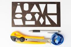 Regla, pluma, metro, cuchillo de los efectos de escritorio en un fondo blanco Imagen plana del diseño con la visión superior Foto de archivo