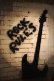 Reglas de la roca con la sombra de la guitarra. Imagen de archivo libre de regalías
