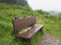 Regn-blött parkera bänken - den Ben Venue synvinkeln - den Trossachs nationalparken - Skottland royaltyfria foton