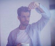Regn för withh för kaffe för morgonen för den avkopplade drinken för den unga mannen tappar första på royaltyfri foto
