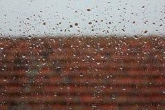 Regn från fönster med taket Arkivbilder