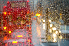 Regn i den London sikten till den röda bussen till och med regn-specked fönster Arkivfoton
