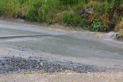 Regn och droppar på vägen Arkivfoto