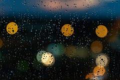 Regn på exponeringsglas med bokehstreetlights royaltyfri fotografi