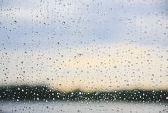 Regn på ett fönster med kustlinjen i bakgrunden och den blåa himlen Arkivfoto