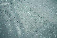 Regn som faller på exponeringsglas (regn-droppar) Arkivfoton