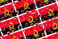 Regn tappar mycket av Angola flaggor arkivfoton