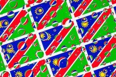 Regn tappar mycket av Namibia flaggor arkivbild